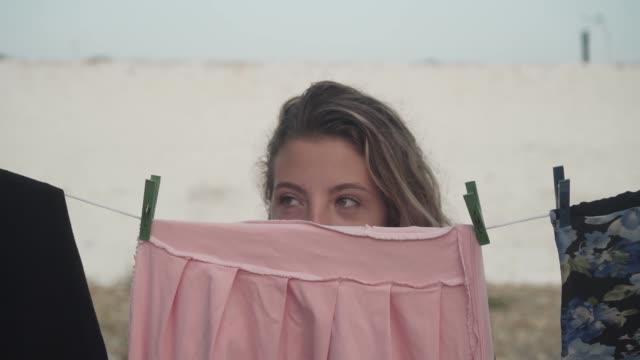 genç bir kız pembe bir elbise çalar, sokakta bir ip üzerinde kurutulur clothespins, onu kaldırarak. - örtmek stok videoları ve detay görüntü çekimi