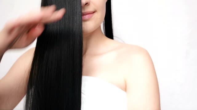 長い髪に手をなでる若い女の子は、その滑らかさと silkiness を発揮します。かなりの女性は髪を気遣う - 髪型点の映像素材/bロール