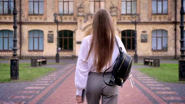 young girl student is going to university in summer, studying concept, back view - struttura pubblica video stock e b–roll
