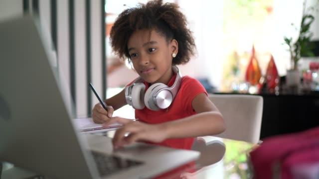 giovane ragazza che studia alle lezioni online a casa - 8 9 anni video stock e b–roll