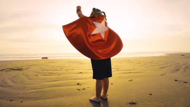 young girl superhero running on california beach - potere femminile video stock e b–roll