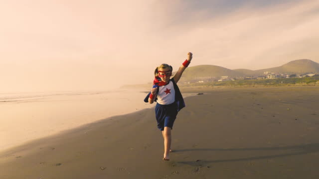 Young Girl Superhero Running on California Beach A young girl dressed as a superhero stands barefoot on a California beach with her arm raised to the blue sky. She is ready to save the world. She is confident and has the strength to overcome all adversity. Video taken at Morro Bay, California. 4K Resolution video. hope concept stock videos & royalty-free footage