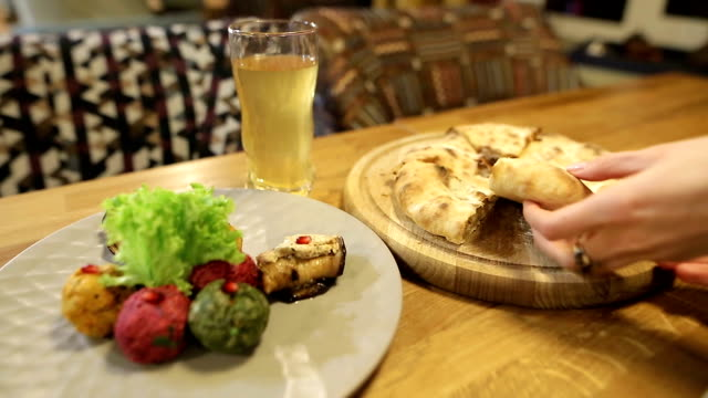 A young girl takes a piece of traditional Georgian khachapuri dish with meat. Multi-colored Pkhali, Georgian dish with nuts and kubdari video