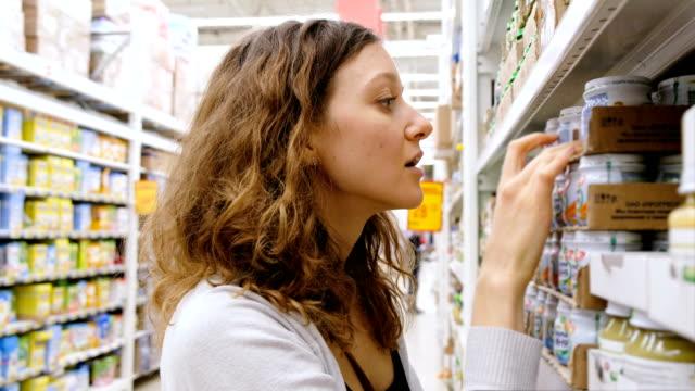 vídeos de stock, filmes e b-roll de uma jovem garota leva a comida de bebê na loja, 4k. - sem glúten