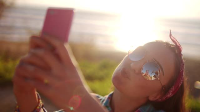 Young girl taking a selfie next to the beach video