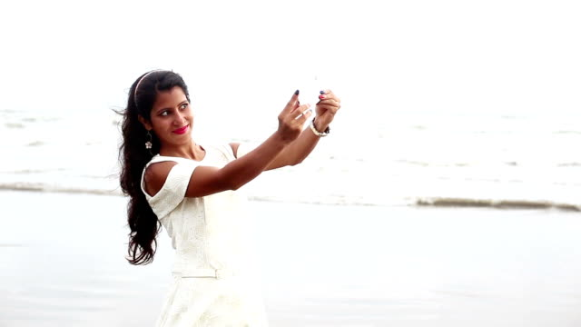 Young girl taking selfie by mobile on tropical sandy beach video