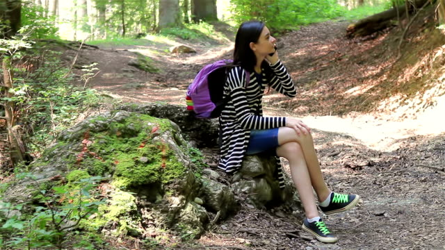 Young girl talking on smartphone in forest video