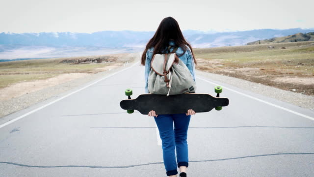 Young girl teenage hipster walks on highway with longboard. With a camp backpack and a jersey jacket. Against the backdrop of snowy mountains. The girl is traveling alone video