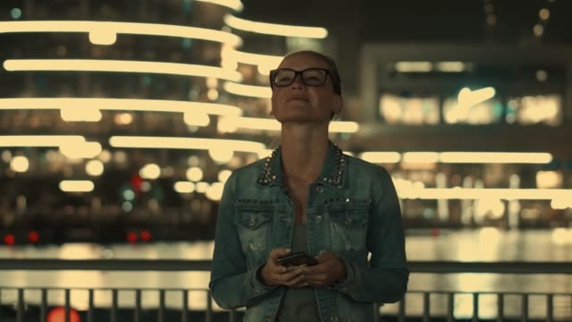 Young girl tourist admiring the view of the beautiful shining night Dubai