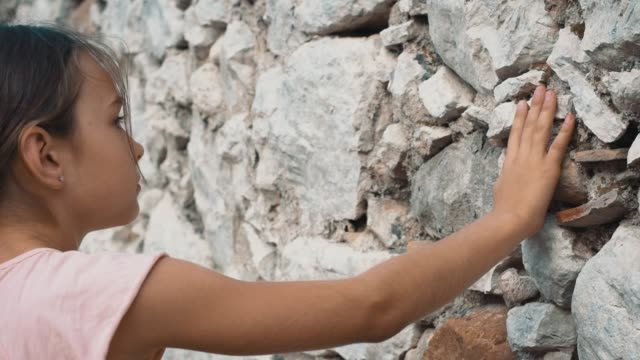 Young girl tourist looking at ancient wall of stone.Teenager in historical place