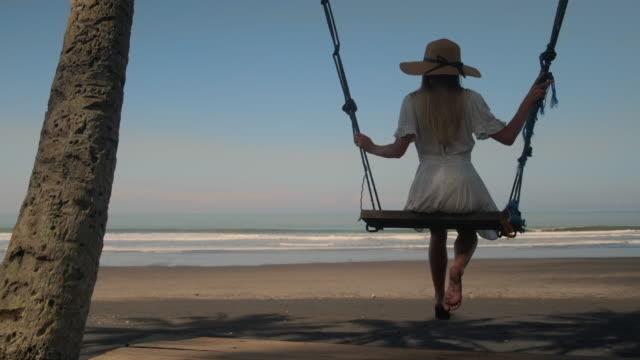 vídeos y material grabado en eventos de stock de joven turista relajante en el columpio en la orilla tropical - espalda humana