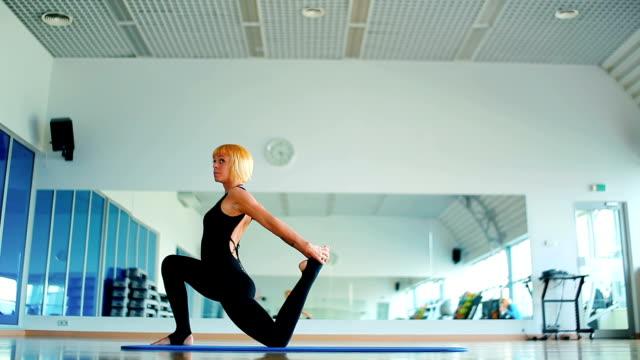 junge mädchen trainieren ihre flexebelie im yoga in der nähe des spiegels auf der matte - haarfarbe stock-videos und b-roll-filmmaterial