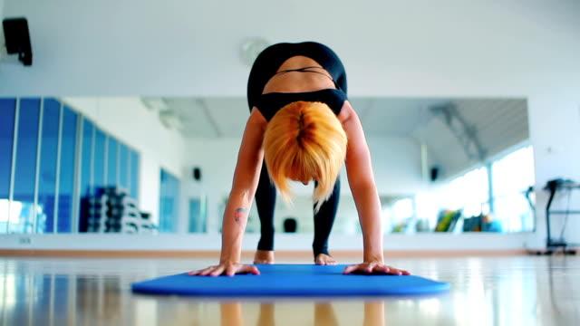 junge mädchen trainieren ihre flexebelie mit yoga in der turnhalle des sports - haarfarbe stock-videos und b-roll-filmmaterial