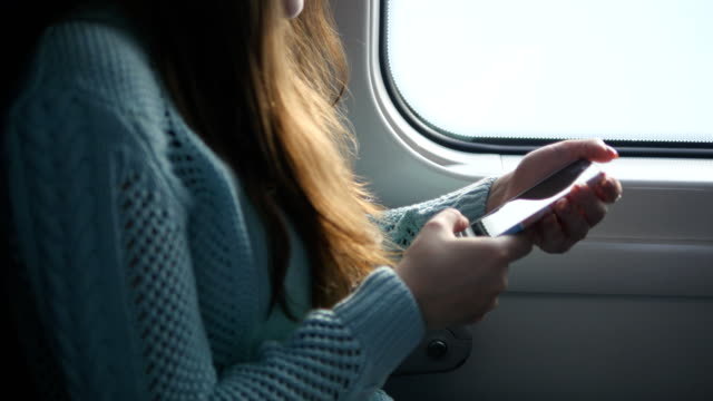 Young girl traveling in a train and using mobile phone. Beautiful woman sends a message from the smartphone. Attractive girl chatting with friends. video