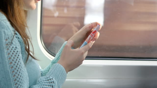 Young girl traveling in a train and using mobile phone. Beautiful woman sends a message from the smartphone. Attractive girl chatting with friends. Passing train at window. Close up video