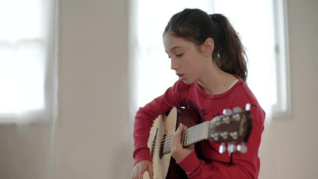 vídeos de stock, filmes e b-roll de jovem garota tentando tocar guitarra, tendo problemas - música acústica