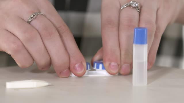 vídeos de stock e filmes b-roll de young girl using contact lenses. bottle with lens solution and case - contacts