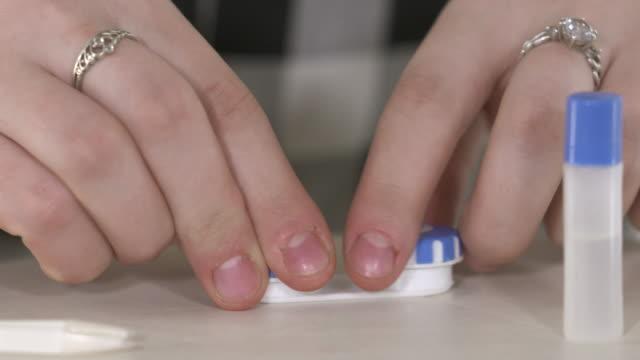 vídeos de stock e filmes b-roll de young girl using contact lenses. inserting contact lense. - contacts