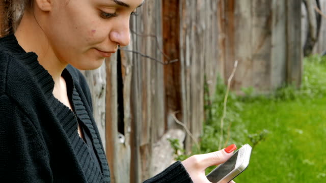 Young girl using her smart phone outdoors video