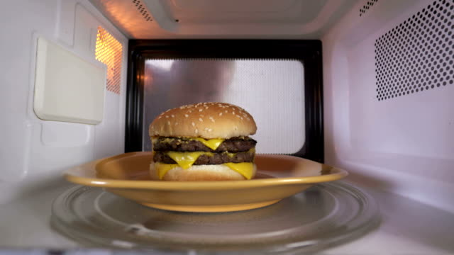 vídeos de stock e filmes b-roll de young girl using microwave for reheating cooked double cheeseburger - hambúrguer comida