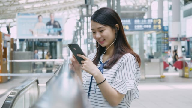 Young girl using mobile phone on platform at Taiwan video