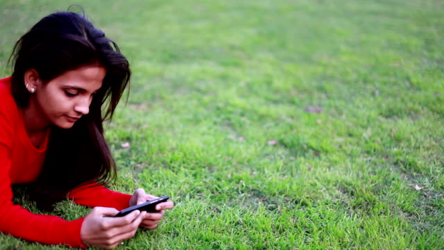 Young girl using smart phone in the park video