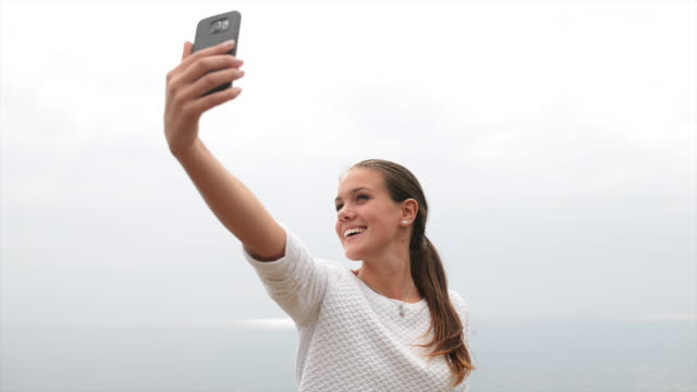 Young girl video messaging using her smart-phone Young girl video messaging using her smartphone from the seashore vanity stock videos & royalty-free footage