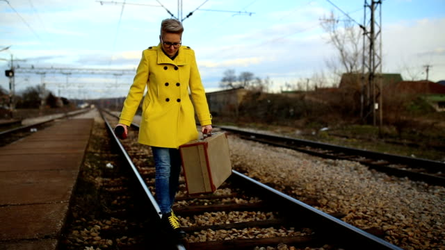 young girl walking along railway station, - donna valigia solitudine video stock e b–roll