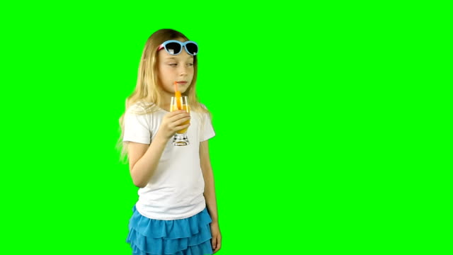 A young girl walks by drinking juice and waving her hand. Clip contains solid green instead alpha channel. video