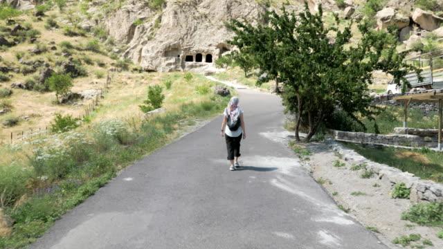 young girl walks in cave monastery vardzia - georgia - obiekt światowego dziedzictwa unesco filmów i materiałów b-roll