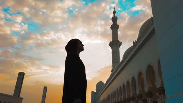 若い女の子は日没時にモスクに歩きます。東への旅 - モスク点の映像素材/bロール