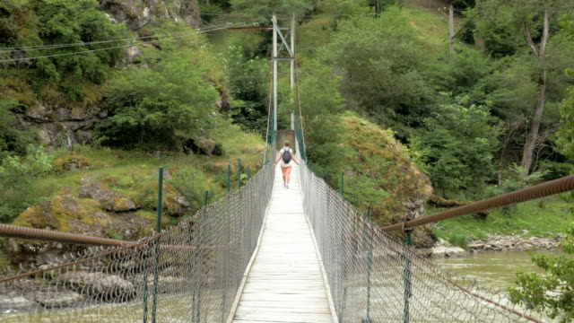 Young girl walks on the suspension bridge - Georgia Young girl walks on the suspension bridge - Georgia. suspension bridge stock videos & royalty-free footage