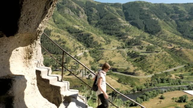 young girl walks the stairs in cave monastery vardzia - georgia - obiekt światowego dziedzictwa unesco filmów i materiałów b-roll