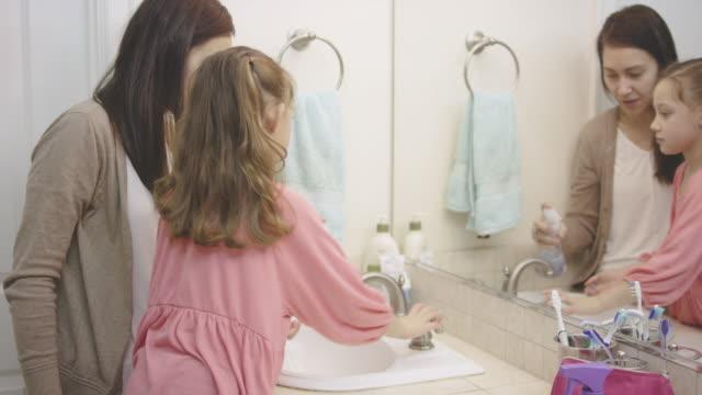 ung flicka handtvätt med sin mamma i badrummet - washing hands bildbanksvideor och videomaterial från bakom kulisserna