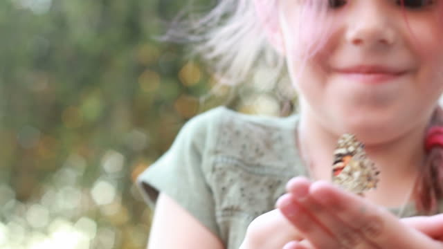 Young girl watches butterfly fly from her hand video