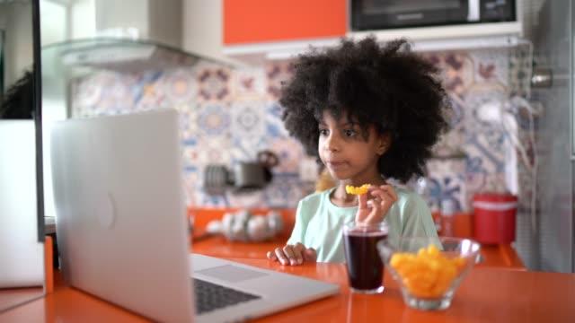 vídeos de stock, filmes e b-roll de jovem assistindo filme em casa no laptop e comendo junk food - comida salgada