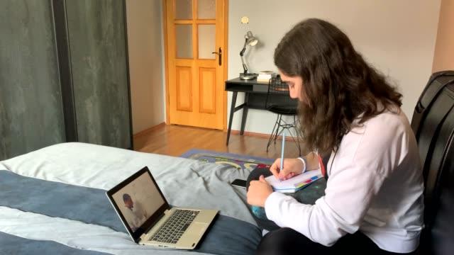 vidéos et rushes de jeune fille observant la leçon en ligne de l'ordinateur à la maison, homeschooling, 4k - 18 19 ans