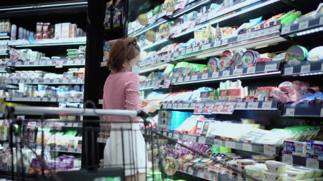 Young girl wearing a protective face mask shopping in supermarket Asian woman protect yourself from the COVID-19 with protective face masks, air pollution and anti-virus concept environmental consciousness stock videos & royalty-free footage