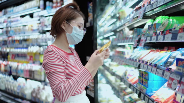 Young girl wearing a protective face mask shopping in supermarket
