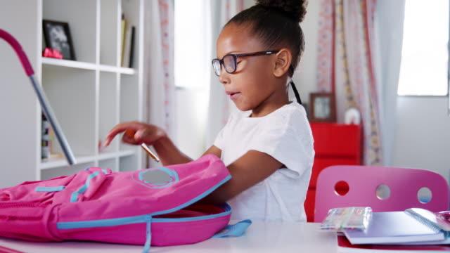genç kız yatak odasında evde okul çantası ambalaj gözlüklü - sırt çantası stok videoları ve detay görüntü çekimi