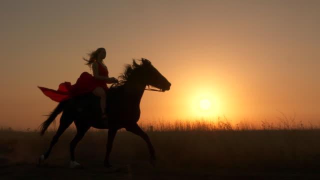 夕日太陽に対して黒い馬に乗って長い赤いドレスを着た少女 ビデオ