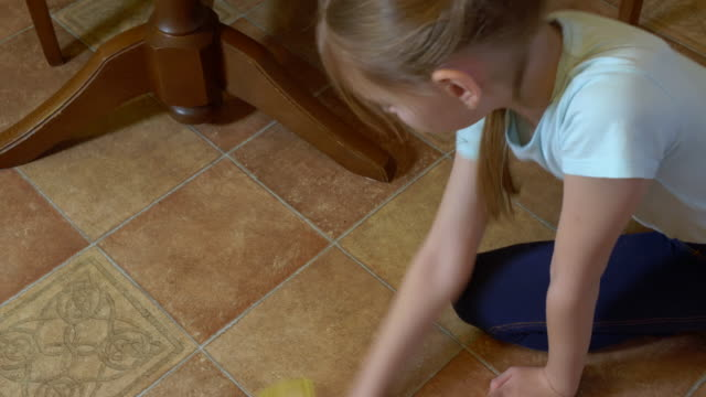 Young girl wiping tiled floor with rag in kitchen. Teenage girl mopping with rag kitchen floor while homework overhead view.