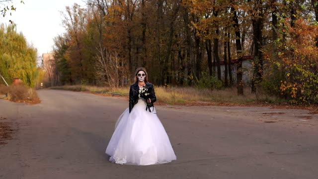 A young girl with a creepy make-up in the form of a skull going on an empty road A young girl with a creepy make-up in the form of a skull on her face in a wedding dress and a leather jacket going on an empty road. Halloween. The image of the dead bride. skull stock videos & royalty-free footage