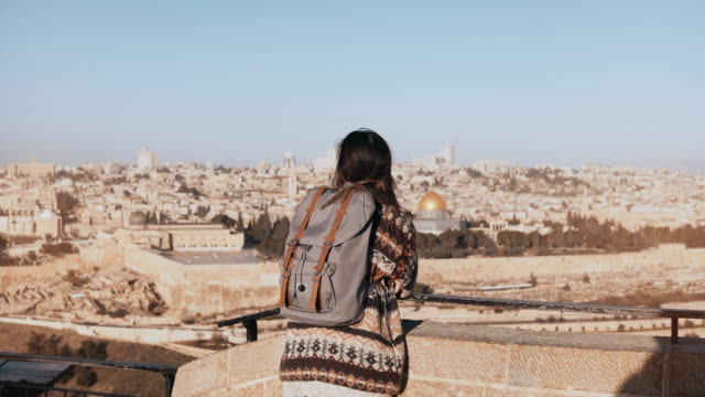 Young girl with backpack enjoys Jerusalem panorama. Thoughtful European tourist looks at ancient old town in Israel. 4K video