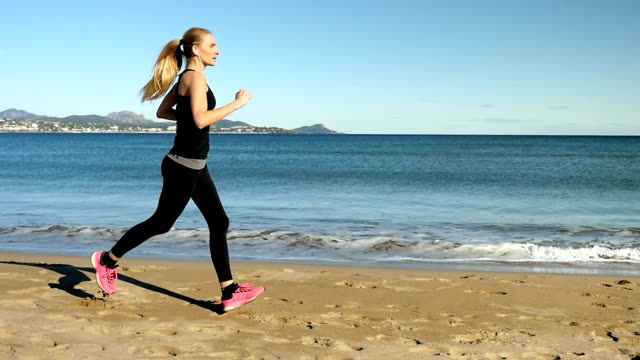 Young girl with earphones and smart watch running on beach video