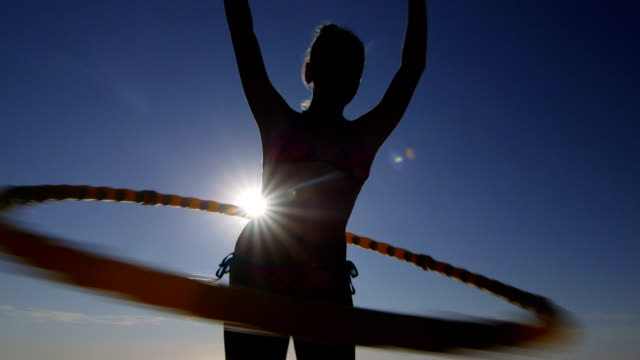 Young girl with massage hula hoop during fitness exercise video