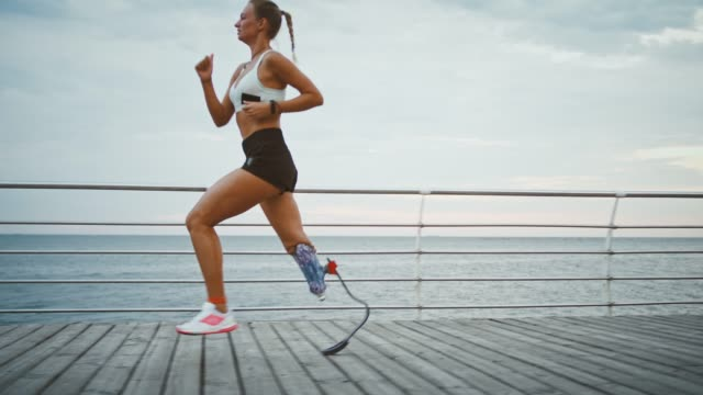 Young girl with prosthetic running on pier near sea