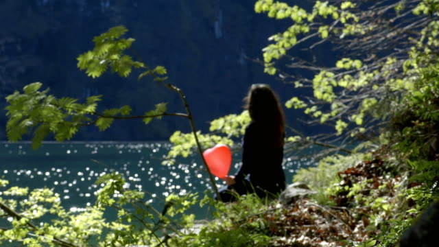 Young girl with red balloon in shape of heart in nature video