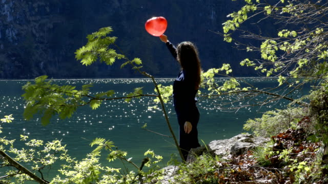 Young girl with red balloon in shape of heart next to the lake video