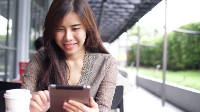 タブレット、コーヒーのカフェに座っている若い女の子 ビデオ